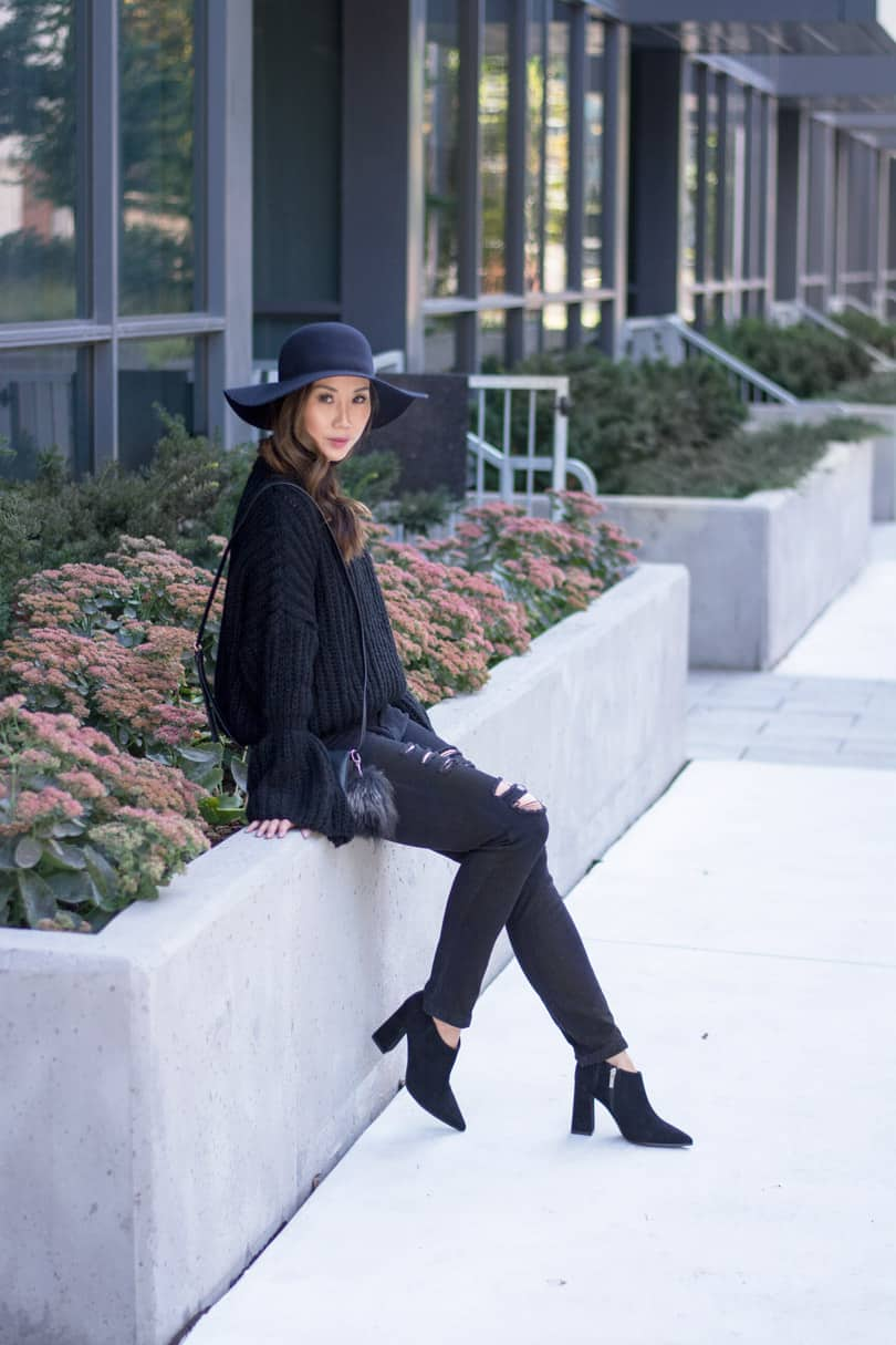 Loving the bell sleeve trend. Fashion blogger fall streetstyle with black bell sleeve sweater and ripped black jeans
