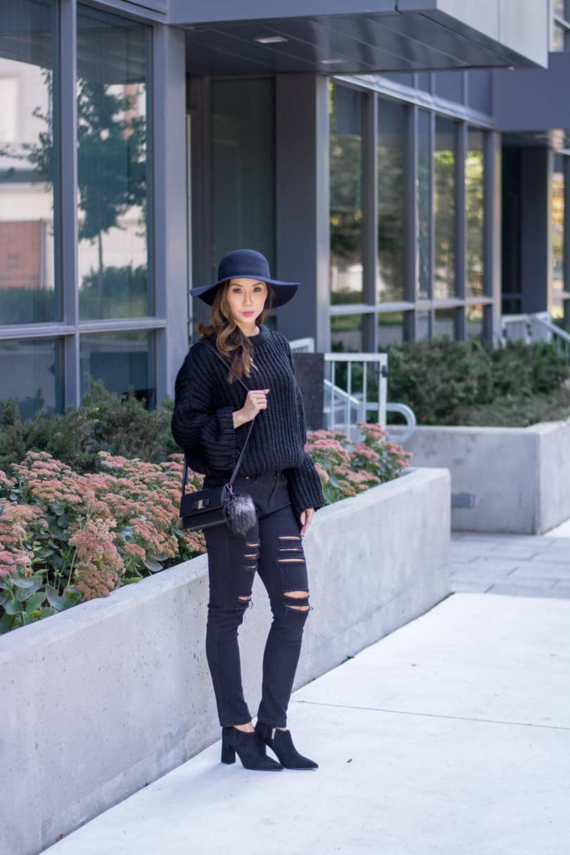 Street style all black look with bell sleeve sweater and ripped jeans