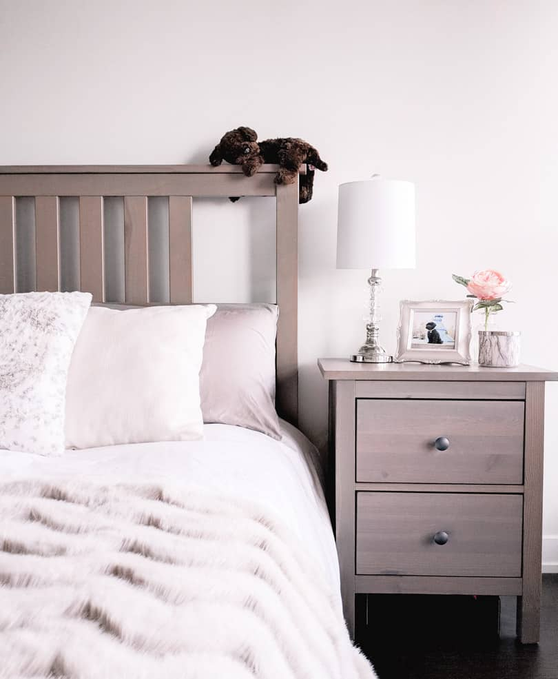 Simple bedroom design with wood night stand and fur throw in cozy neutral tones.