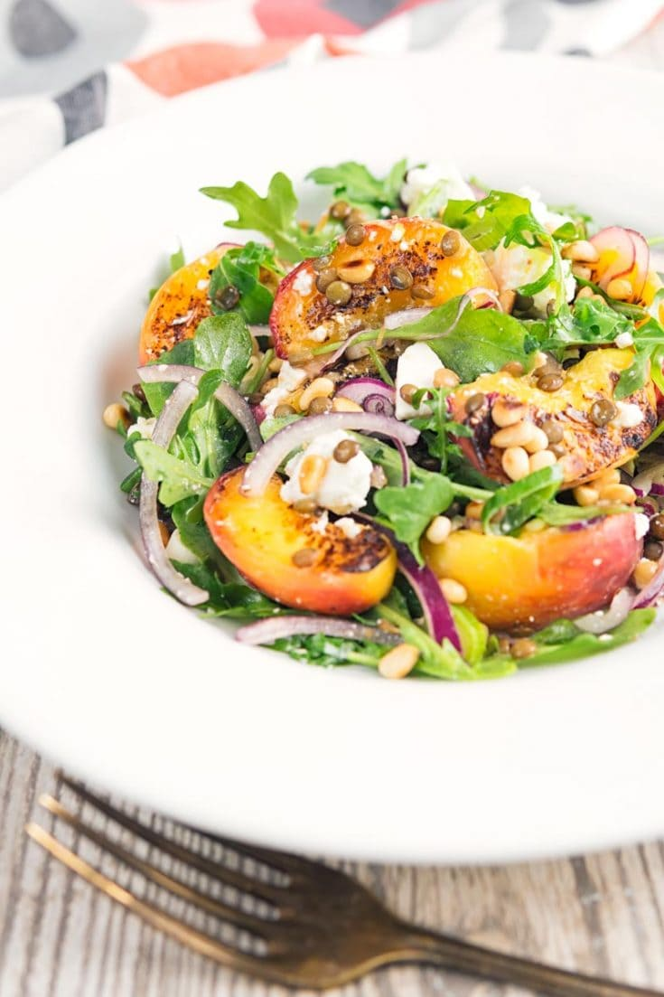 Try this delicious, easy salad recipe - pan-fried peach and feta salad with arugula, puy lentils and toasted pine nuts served in a white bowl